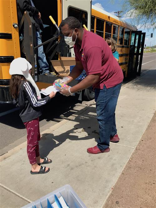 CNS employee distributing food to students